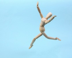 Cheerful wooden puppet jumping on blue background