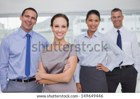 Cheerful work team posing together in bright office - stock photo