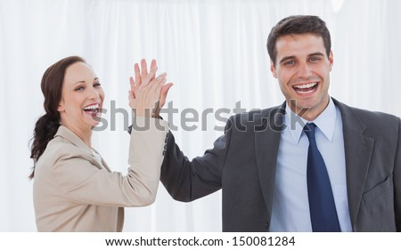 Cheerful workmates doing high five in bright office