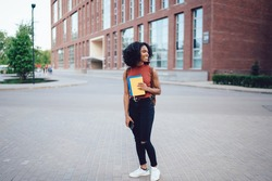 Cheerful young African American female undergraduate with Afro hairstyle looking away while holding cellphone and notebooks and standing near college campus