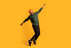Cheerful young african american man in orange hat standing on tiptoes over yellow background, full length shot of happy millennial black hipster guy dancing and having fun in studio, copy space