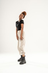 Cheerful young african american woman girl smiling and posing in comfortable casual clothes. People sincere emotions lifestyle concept. A lot of copy space on a white studio background.