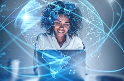 Cheerful young African American woman using laptop in blurry office with double exposure of futuristic network interface and planet hologram. Concept of internet and communication. Toned image