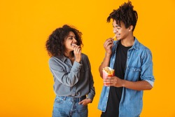 Cheerful young african couple standing isolated over orange background, eating french fries