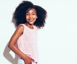 Cheerful young African girl with long curly hair smiling confidently while standing alone against a white background
