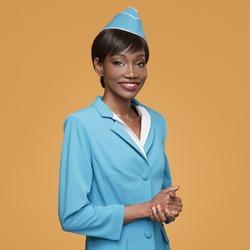 Cheerful young african stewardess. Orange background.