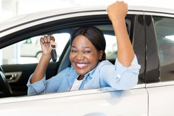 cheerful young african woman showing her new car key at dealership