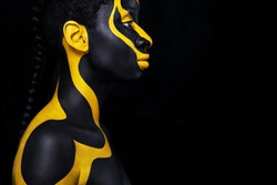 Cheerful young african woman with art fashion makeup. An amazing woman with black and yellow makeup