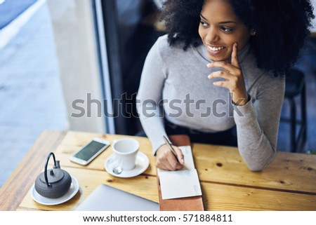 Cheerful young afro american female writer inspiring by good mood and sunny morning while starting to work in cafe continue writing her new detective novel for book house while drinking hot tea