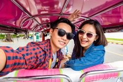 Cheerful young Asian couple tourists taking selfie while traveling on local colorful Tuk Tuk taxi exploring Bangkok city, Thailand