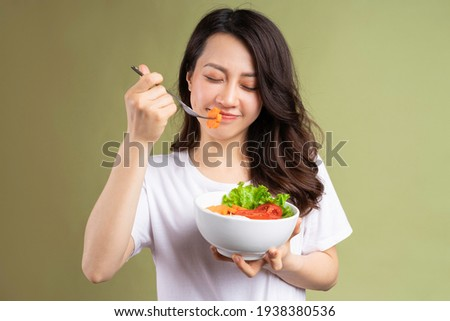 Cheerful young asian girl eating health food on background