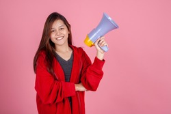 Cheerful young Asian woman or teen or college student with megaphone on pink background. Leader Team Power Lifestyle Speaker and Teenager Concept
