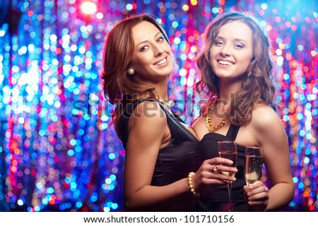 Cheerful young beauties with flutes of champagne having a nightclub party