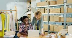 Cheerful young beautiful African American woman manager worker working in clothing shop sitting at desk browsing on laptop and speaking with Caucasian happy female boss designer, fashion business