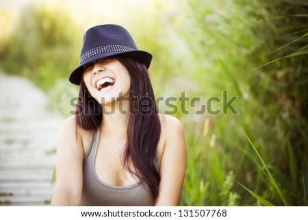 Cheerful young beautiful woman in nature - stock photo