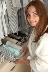Cheerful young beautiful woman is holding a container with things during spring cleaning in a closet. The concept of ideal ordering and organizing storage of things