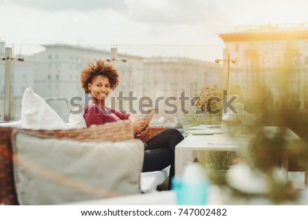 Cheerful young black freelancer woman using digital tablet while sitting in street cafe on the roof; Brazilian smiling female student with digital pad in luxury street bar on the top of building