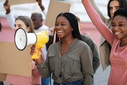 Cheerful young black lady leading international group of protestors, chanting slogans through megaphone. Active multiracial students with empty placards having strike or demonstration on the street