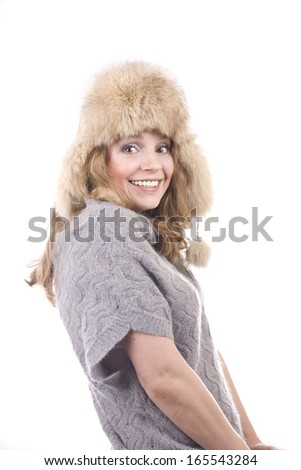cheerful young blond woman in a fur hat on white background #165543284