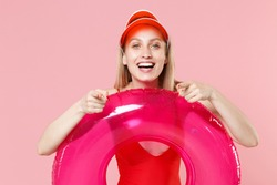 Cheerful young blonde woman girl in red one-piece swimsuit cap isolated on pink background. People summer vacation rest lifestyle concept. Hold swim inflatable ring, pointing index finger on camera