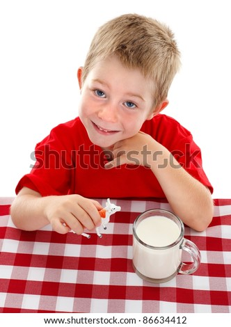 Cheerful young boy looking up, holding toy cow beside big glass cup of milk