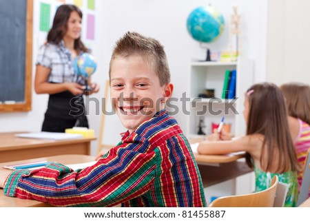 Cheerful young boy smiling in classroom while the teacher explains - stock photo