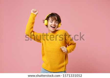 Cheerful young brunette woman girl in yellow sweater posing isolated on pastel pink wall background studio portait. People lifestyle concept. Mock up copy space. Listen music with headphones, dancing