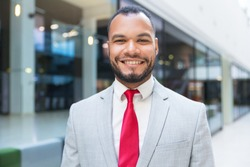 Cheerful young businessman smiling at camera. Portrait of confident African American businessman in suit standing outside office building and looking at camera. Business concept