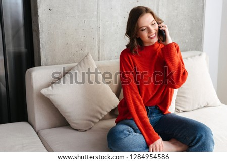 Cheerful young casually dressed woman sitting on a couch at home, talking on mobile phone #1284954586