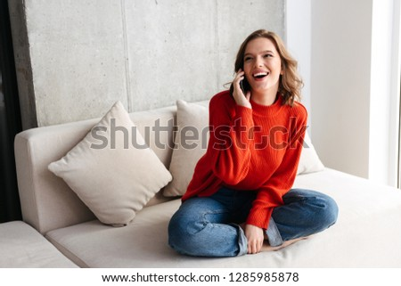 Cheerful young casually dressed woman sitting on a couch at home, talking on mobile phone