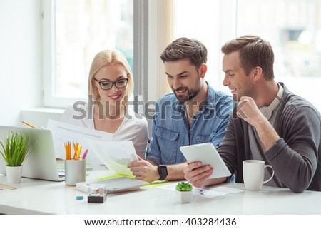 Cheerful young colleagues are doing paperwork #403284436