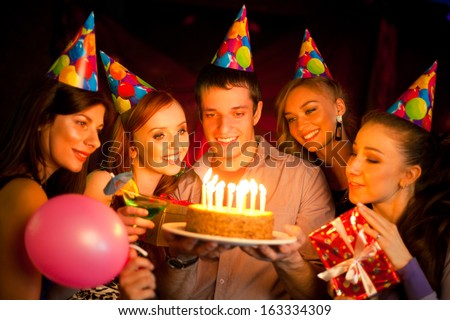 cheerful young company celebrates birthday and have a cake with candles