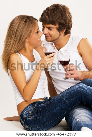 Cheerful young couple drinking wine, neutral background