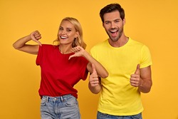 Cheerful young couple friends guy girl in yellow red t-shirts isolated on yellow background studio portrait. People lifestyle concept. Mock up copy space. Pointing thumbs on herself, showing thumbs up
