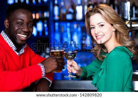 Cheerful young couple having cocktail at a restaurant bar.