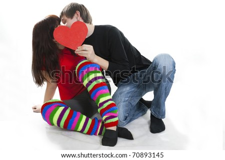 cheerful young couple hiding their kiss by red heart