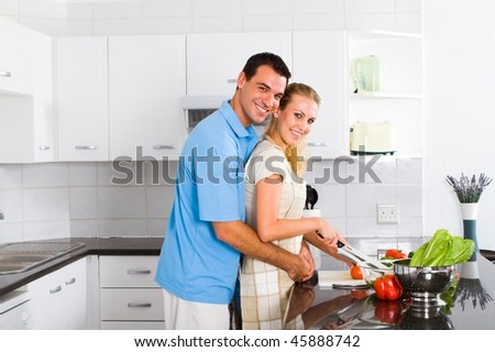 cheerful young couple in home kitchen - stock photo