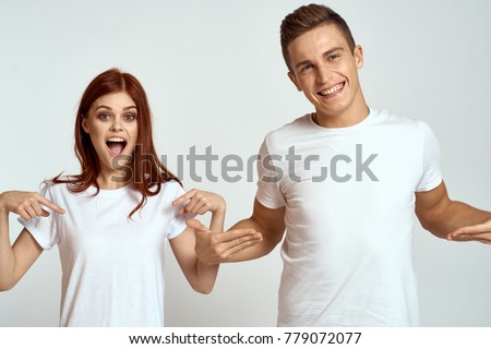 cheerful young couple in white t-shirts on a light background, logo