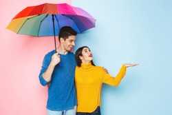 Cheerful young couple isolated over two colored background, standing under an umbrella