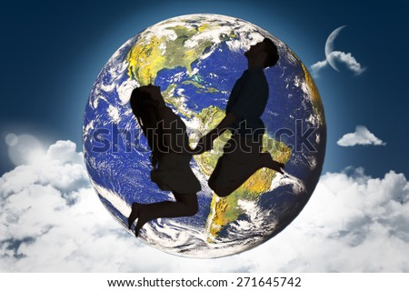 Cheerful young couple jumping against night sky
