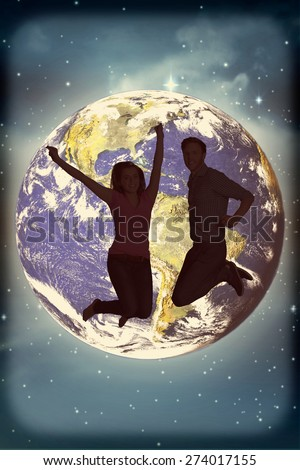 Cheerful young couple jumping against stars twinkling in night sky