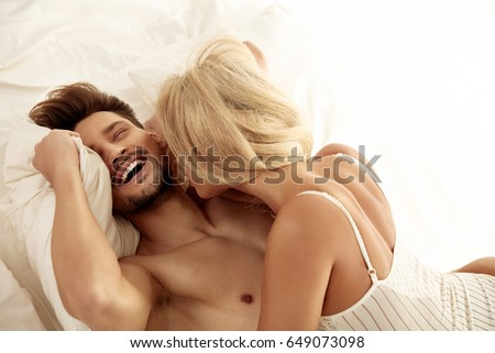 Cheerful young couple resting in the hotel's bedroom