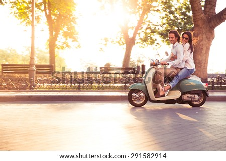 Cheerful young couple riding a scooter and having fun. Sun is shining in the morning
