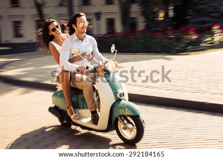 Cheerful young couple riding a scooter in town with fun