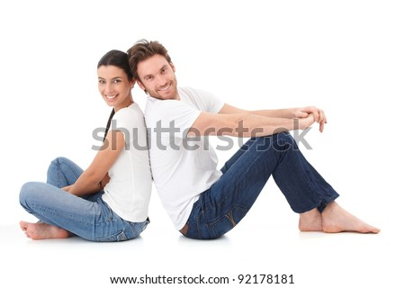 Cheerful young couple sitting with back to each other on floor, smiling happily.?