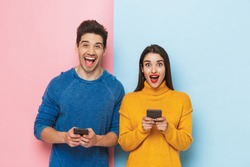Cheerful young couple standing isolated over two colored background, holding mobile phones