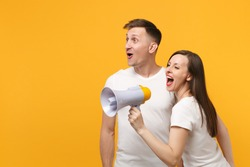 Cheerful young couple two friends guy girl in white empty blank design t-shirts posing isolated on yellow orange wall background. People lifestyle concept. Mock up copy space. Screaming in megaphone