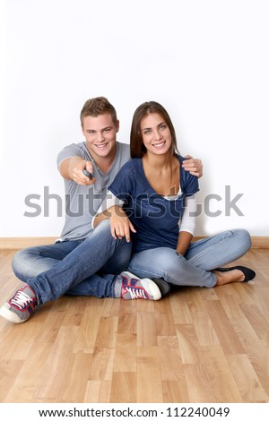 Cheerful young couple using tv remote control - stock photo