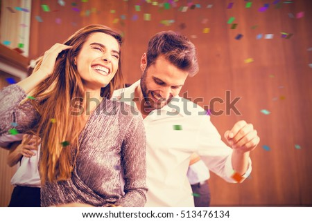 Cheerful young dancing couple against flying colours