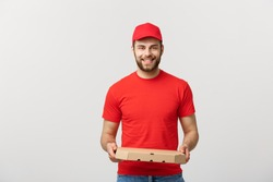 Cheerful young deliveryman holding pizza boxes while isolated on white studio background